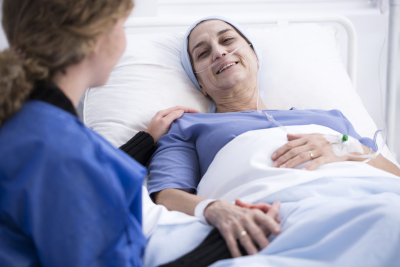 Smiling sick women enjoying a visit of her caregiver supporting her during chemotherapy