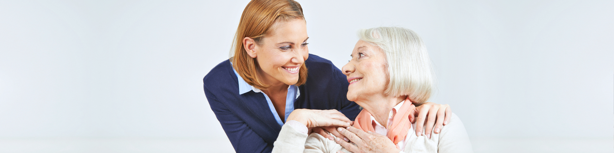 senior woman smiling to her caregiver